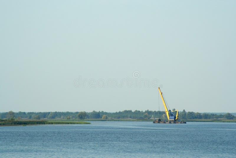 Excavatrice sur la rivière pour l'extraction de sable image libre de droits
