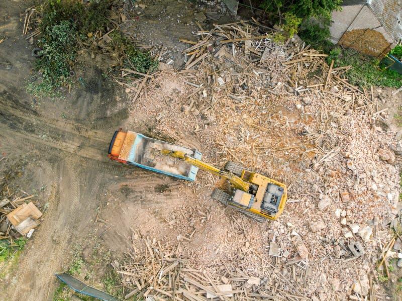 Excavatrice travaillant au chantier de démolition et aux débris de chargement dans le dum image stock