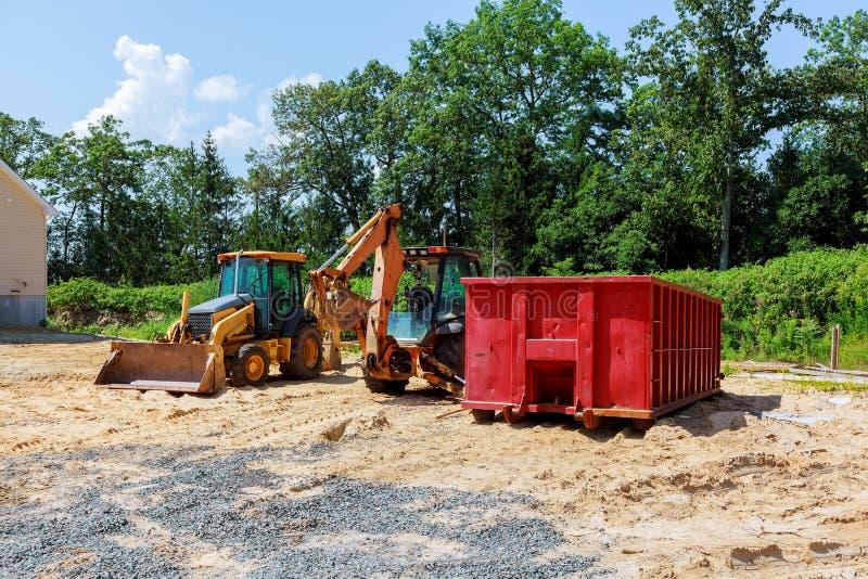 Excavatrices de tracteur de nouvelle construction d'excavatrice et récipients jaunes de déchets images libres de droits