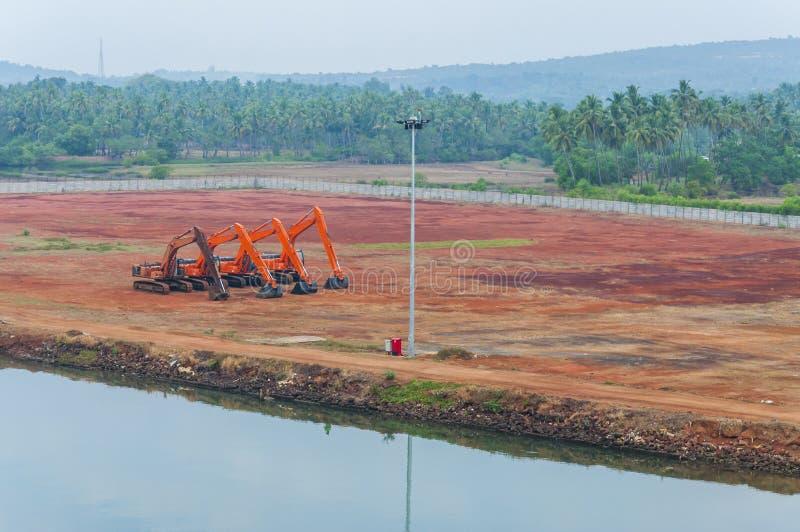 Excavatrices oranges sur un chantier de construction près de la berge image stock