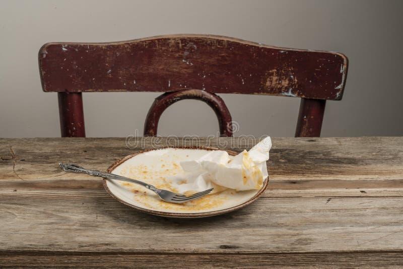 Excedentes izquierdos en la tabla de madera después de la cena foto de archivo