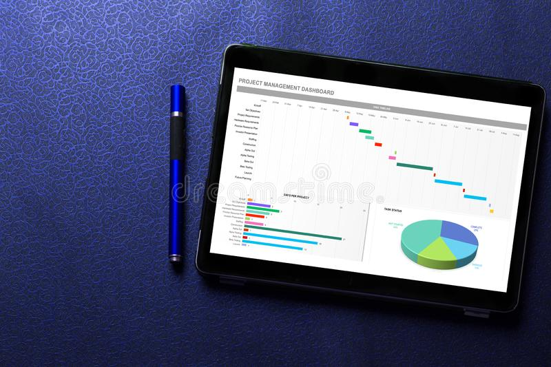 Excel project dashboard concept on tablet screen with blue pen on blue pattern. Textured background stock image