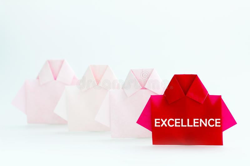 The EXCELLENCE word on One Red among white origami shirt paper ,. EXCELLENCE word on One Red among white origami shirt paper , unique individuality and stock image