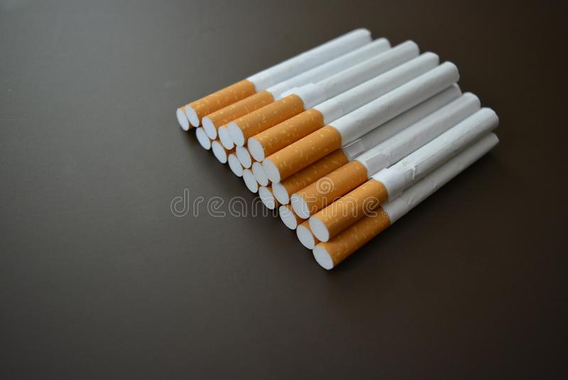 Cigarettes lying in a bunch on a brown matte background royalty free stock images