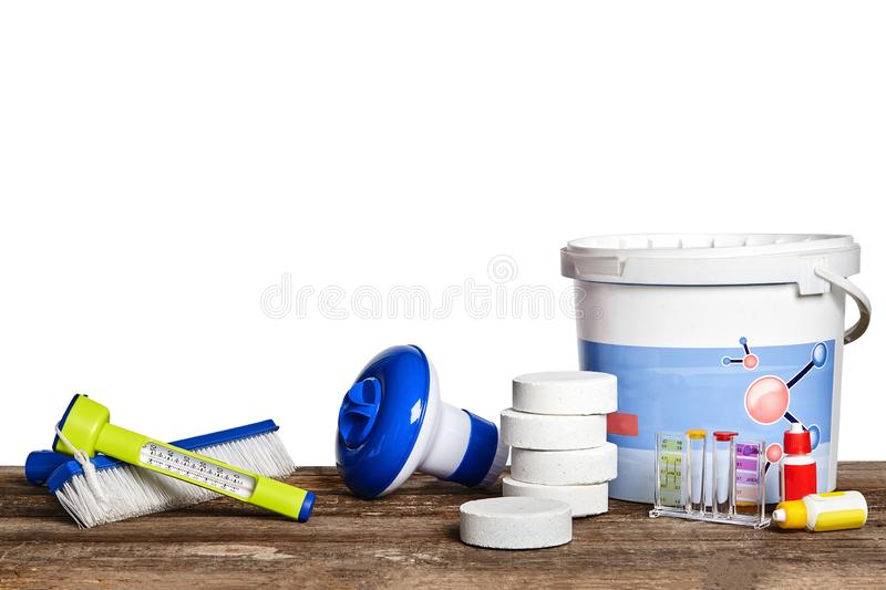 Equipment with chemical cleaning products and tools for the maintenance of the swimming pool on a wooden surface against. Excellent equipment with chemical royalty free stock image