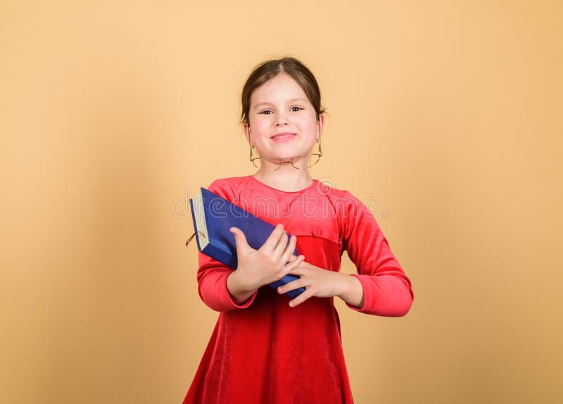 Excellent nerd. Favorite fairytale. Adorable girl love books. Kid girl with book or notepad. Back to school concept. Reading book as hobby. Girlish bestseller royalty free stock image