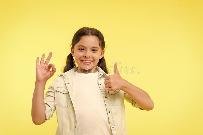 Excellent quality. Kid girl shows thumb up and ok gesture yellow background. Child highly recommend excellent quality. Girl happy smiling recommend high royalty free stock photo