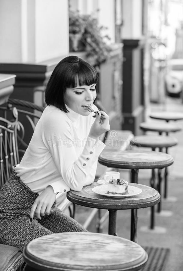 Excellent taste. Woman attractive elegant brunette eat gourmet cake cafe terrace background. Pleasant time and. Relaxation. Delicious gourmet cake. Girl relax stock image