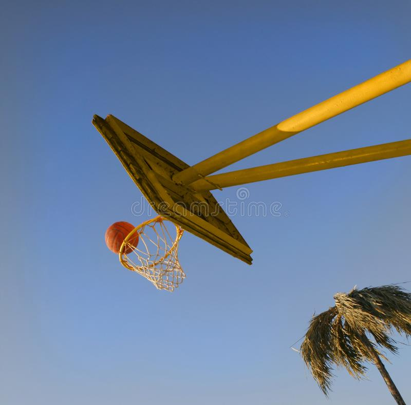 The basketball ball an exact throw gets to a basket. On big dark blue sky royalty free stock images