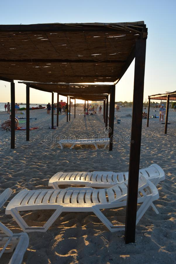 White beach loungers under a canopy on the beach, the coast of the Black Sea at sunset royalty free stock image