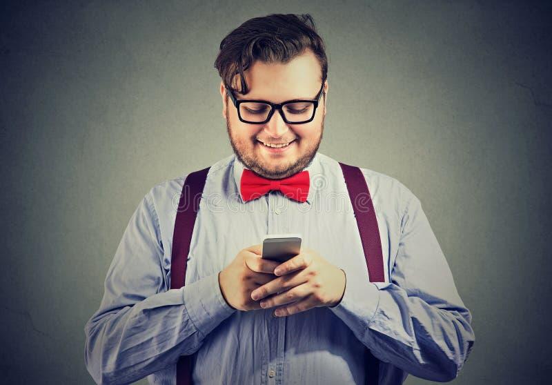 Excentrisk man som använder mobiltelefonen och att le arkivbild
