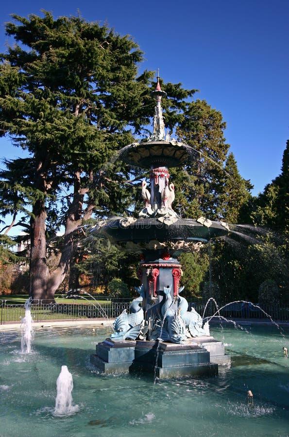Excentrisk påfågelspringbrunn som framme kör av de gröna träden i Christchurch botaniska trädgårdar, Nya Zeeland royaltyfri foto