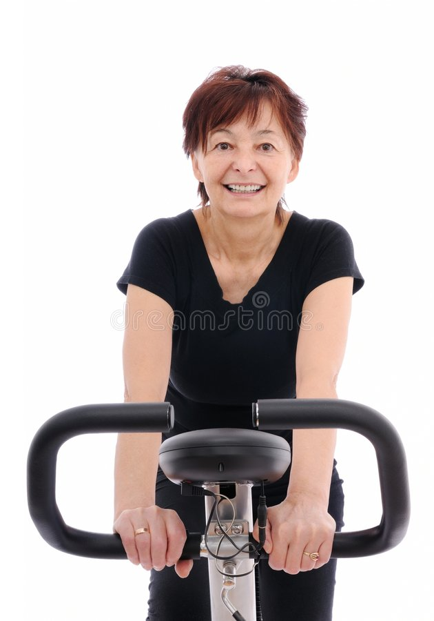 Excercise - spinning senior woman stock images