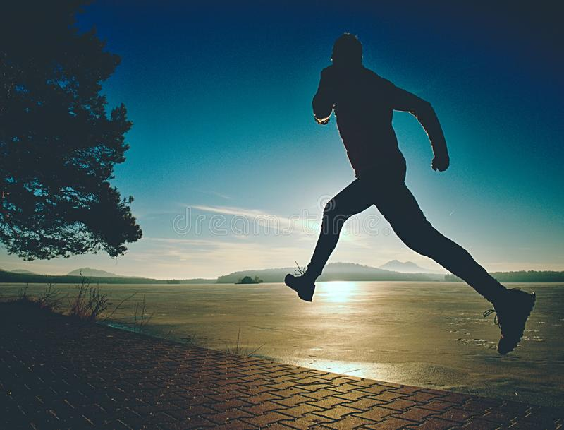 Excercising silhouette against morning sun at bay shore royalty free stock photos