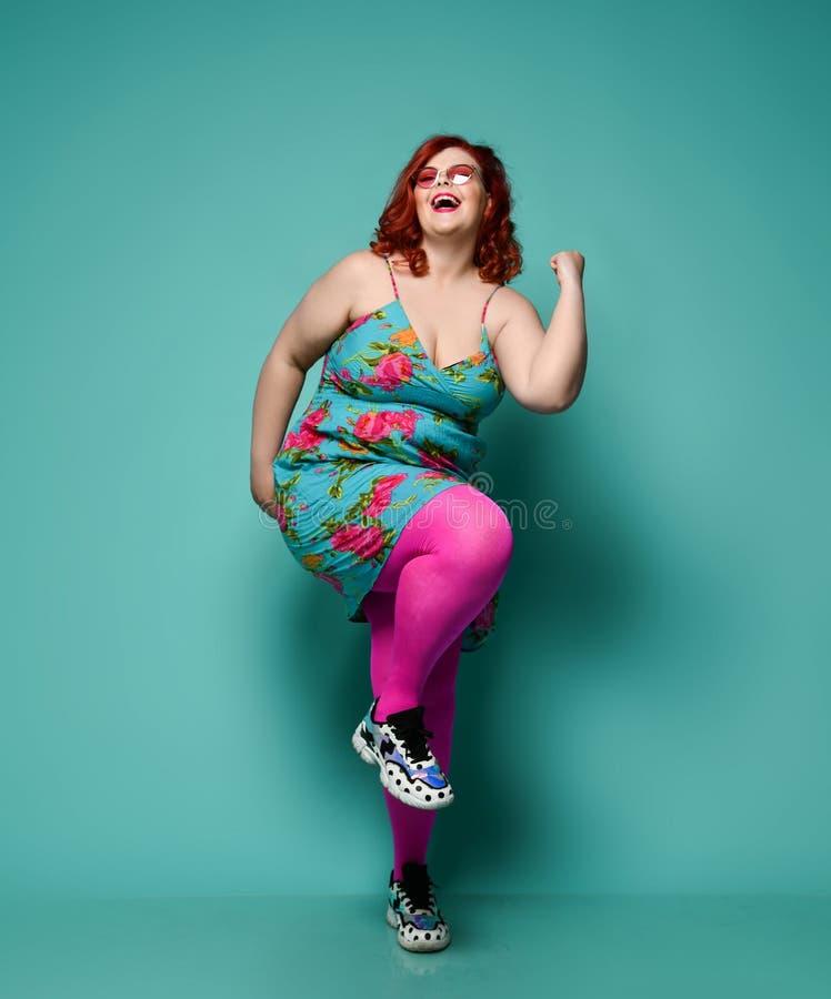Excesso de peso de riso da mulher do ruivo do mais-tamanho na dan?a feliz dos ?culos de sol e da roupa da forma que mostra yeah o fotografia de stock