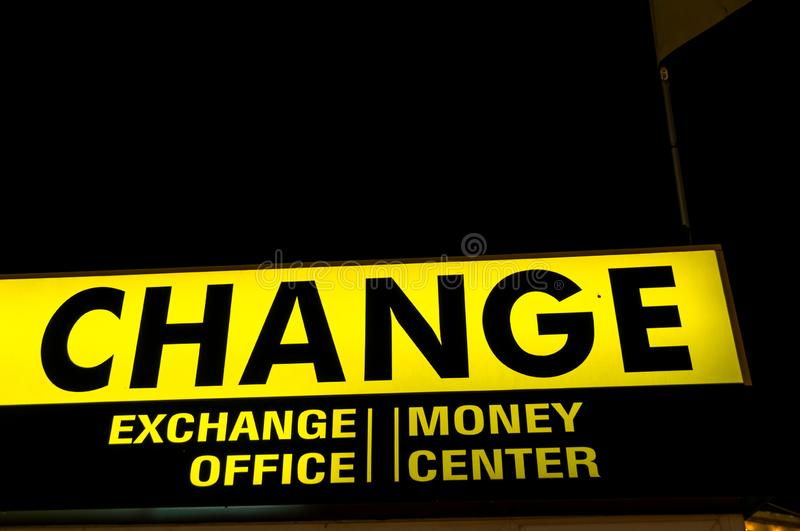 Exchange money center. Finance theme. Glowing Lettering `Change` - the office to exchange money in the streets. Yellow-black letters and background stock image