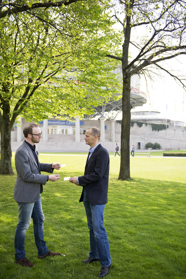 Exchanging business cards. Two business men exchanging business cards at a convention center stock photography