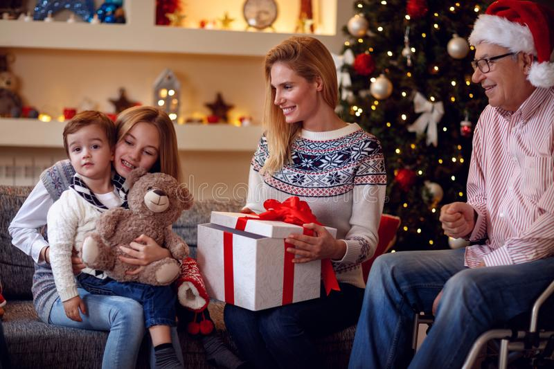 Exchanging Christmas Gifts–family at Christmas opening gifts t. Exchanging Christmas Gifts– happy family at Christmas opening gifts together stock image