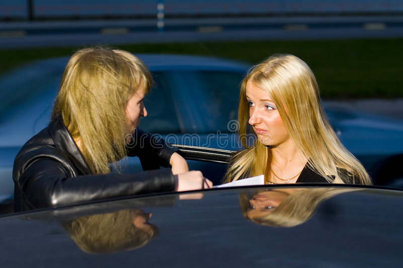 Exchanging Information. Two women exchanging information regarding their vehicles following an automobile accident involving their cars royalty free stock image