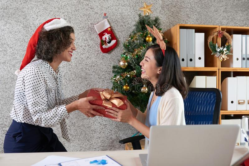 Exchanging presents. Smiling pretty businesswoman giving coworker Christmas present at office party stock image