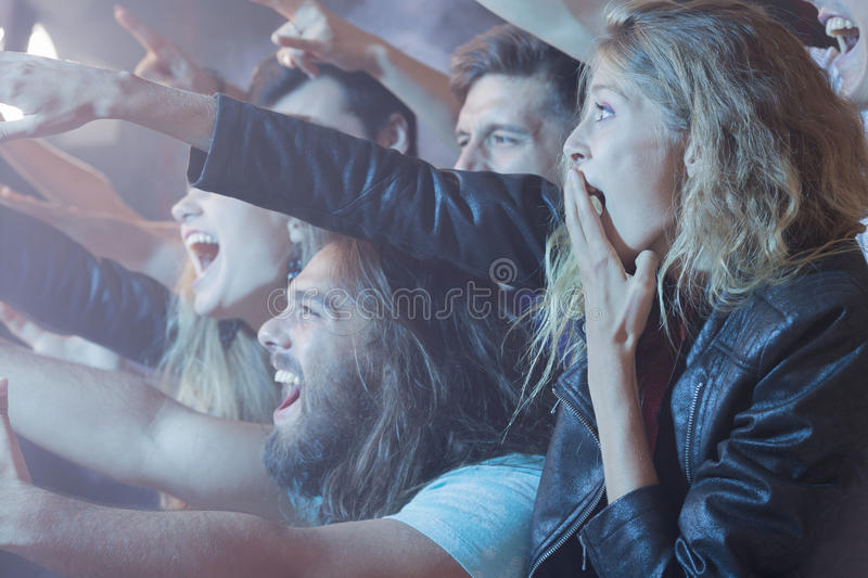 Excidet people stanting at rock concert royalty free stock photography