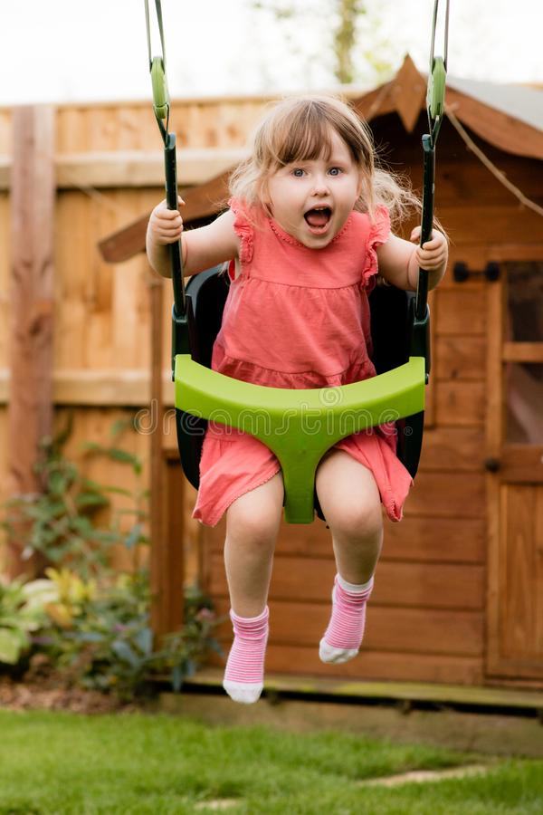 An excitable young girl laughing while playing on the swings royalty free stock image