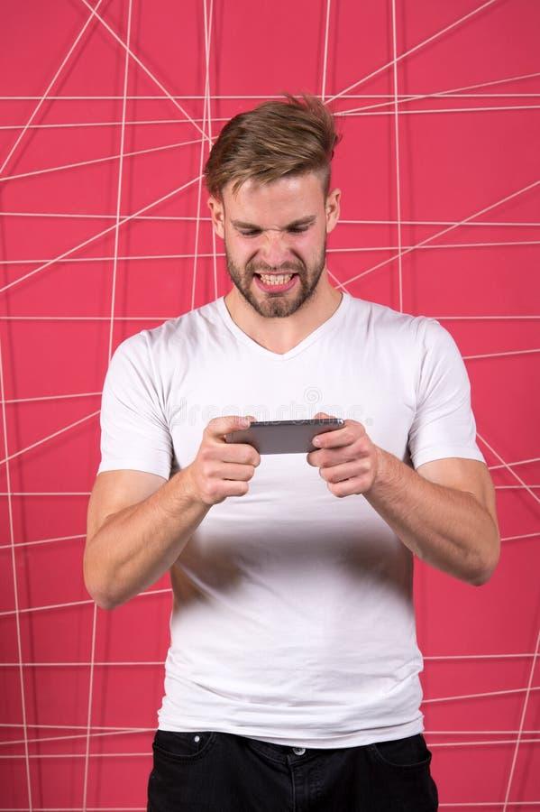 Excitado sobre juego Artilugio del smartphone del juego del juego del individuo Smartphone agresivo del juego online del juego de imágenes de archivo libres de regalías