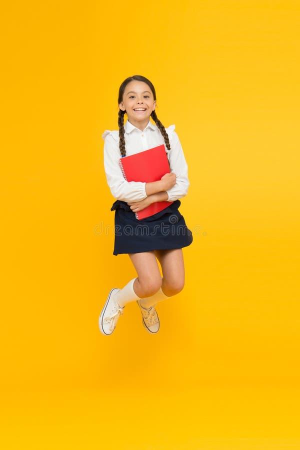 Excitado sobre o estudo Criança feliz que salta na farda da escola Tendo o divertimento Salto e sentimento livre De volta ? escol foto de stock royalty free