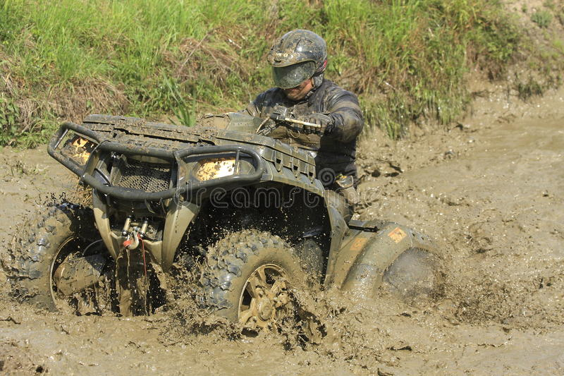 Excitador do four-wheeler da raça na poça da lama foto de stock