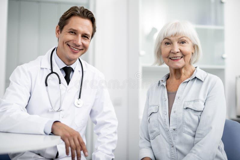 Excited åldrig kvinna som ler, medan sitta med den vänliga doktorn royaltyfri fotografi