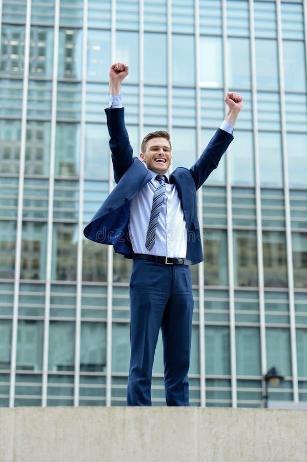 Excited бизнесмен поднимая его оружия стоковое фото