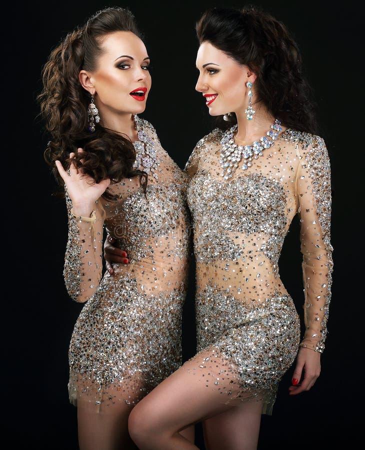 Excited блестящие пары в говорить платьев платины стоковые фотографии rf