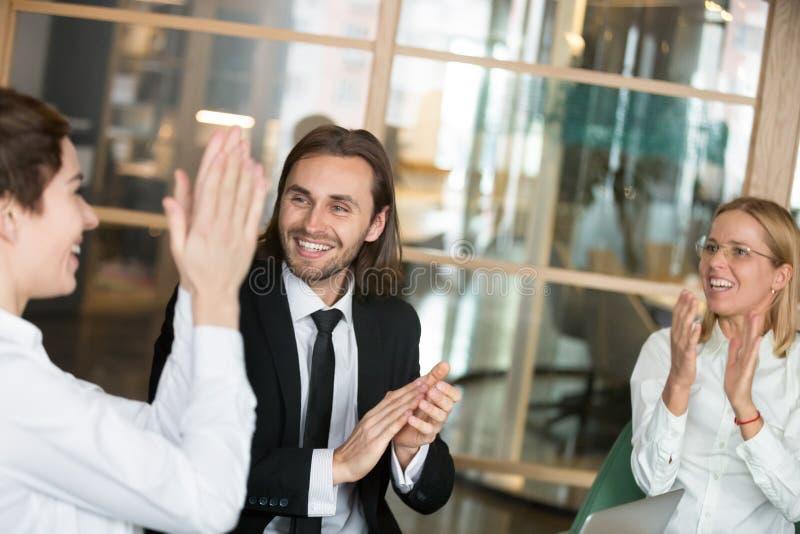 Excited деловые партнеры аплодируя поздравляющ wi коллеги стоковое изображение