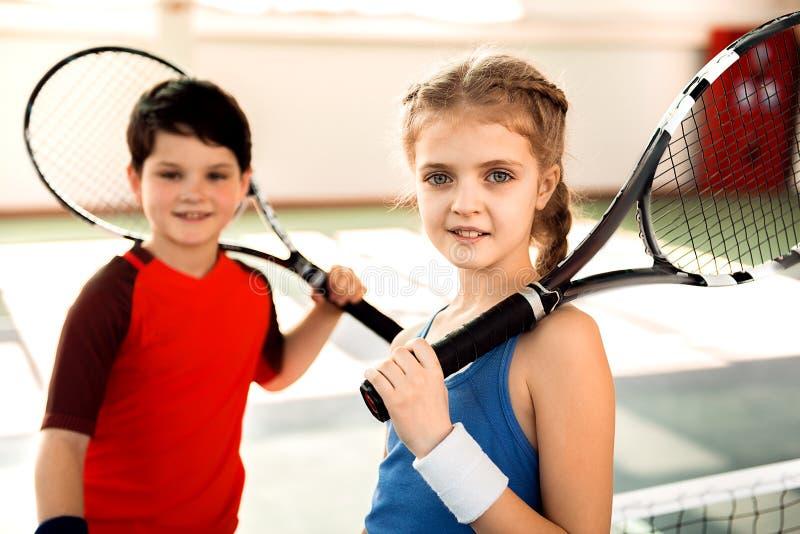 Excited дети играя теннис на суде стоковая фотография