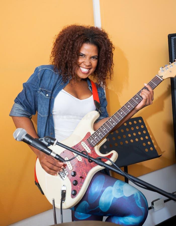 Excited женская играя гитара в студии звукозаписи стоковое фото rf