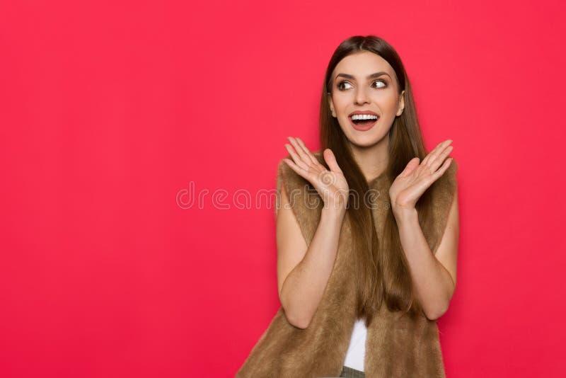 Excited женщина в жилете меха Брайна смотря прочь стоковое изображение