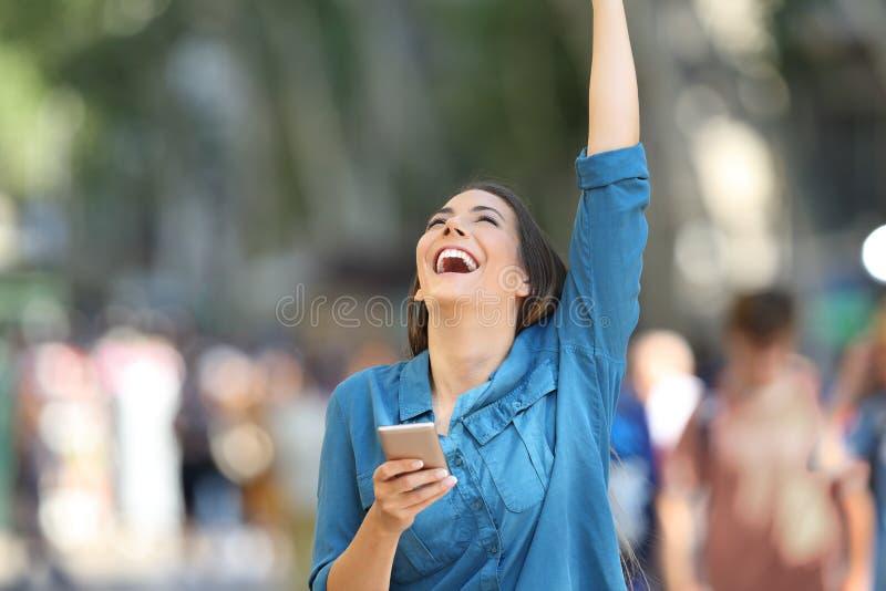 Excited женщина держа телефон и поднимая руку стоковое фото rf