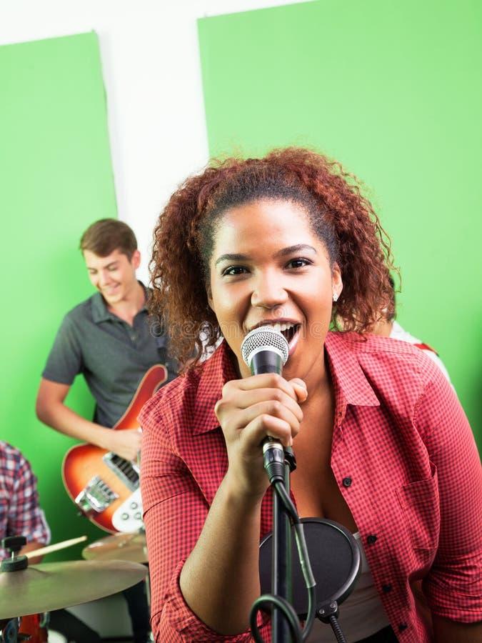 Excited женщина поя в студии звукозаписи стоковое фото