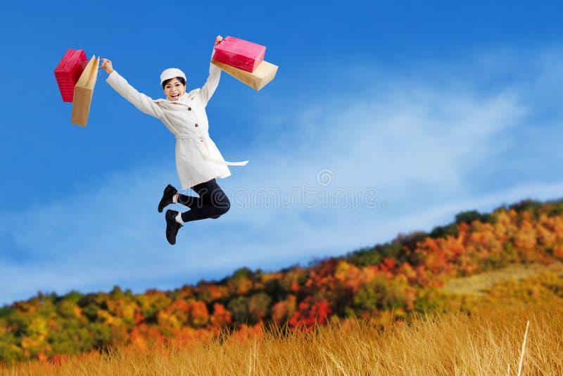 Excited женщина скачет с хозяйственными сумками стоковые фото