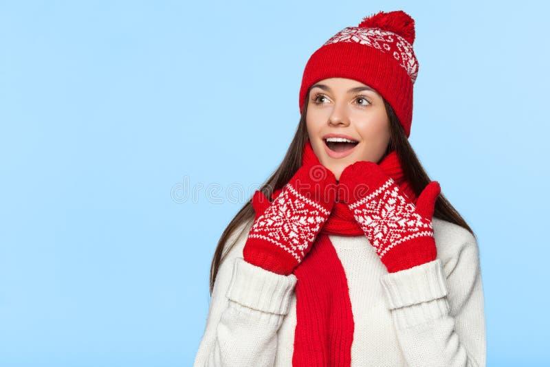 Excited женщина смотря косой в ободрении Удивленная девушка рождества нося связанную теплые шляпу и шарф, изолированные на сини стоковые фото