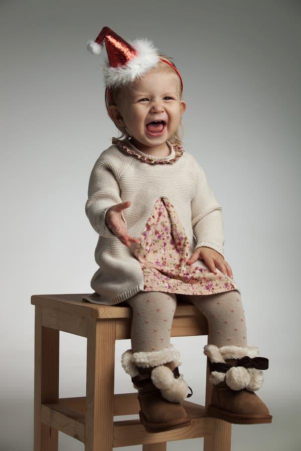 Excited маленькая девочка нося шляпу santa кричаща пока сидящ стоковые изображения