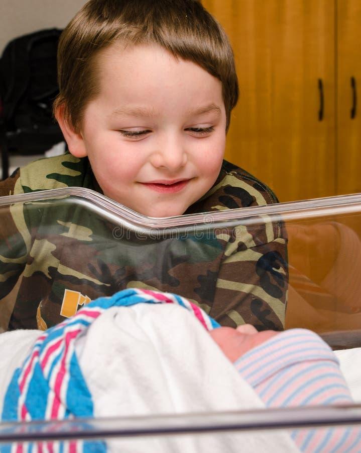 Excited мальчик встречает его младенческий отпрыска после поставки стоковые изображения