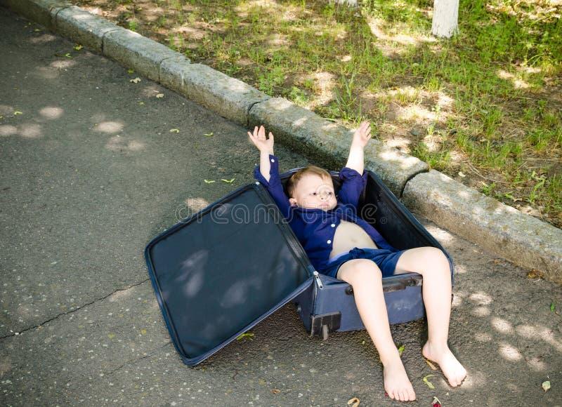 Excited мальчик лежа в веселить чемодана стоковая фотография rf