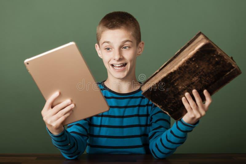 Excited мальчик сравнивая 2 книги стоковые изображения