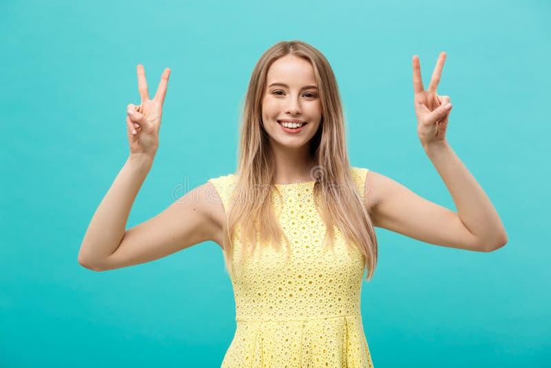 Excited молодая женщина в желтом платье показывая знак руки мира Студия длины 3 кварталов снятая на предпосылке teal стоковые фото