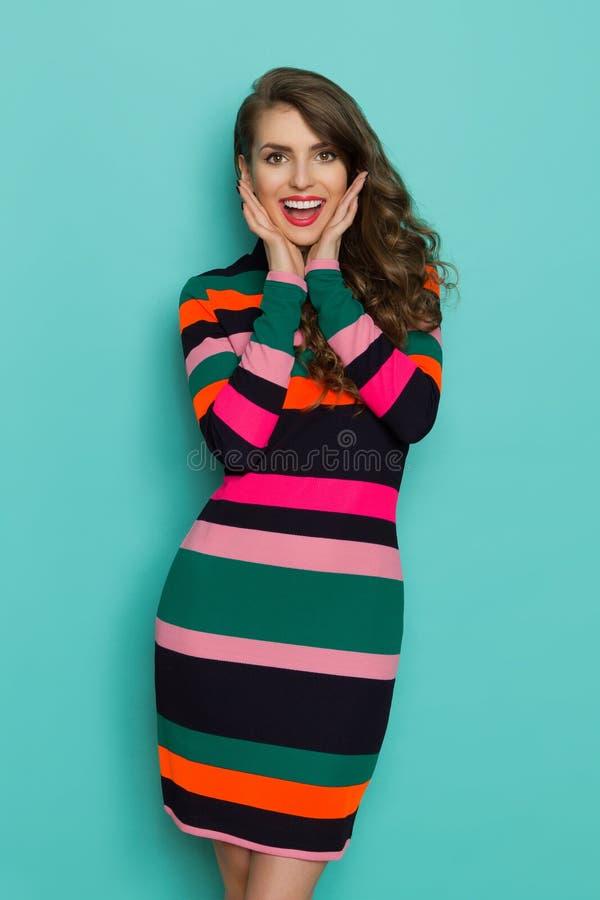 Excited молодая женщина в живом Striped платье держит головной в руках стоковая фотография