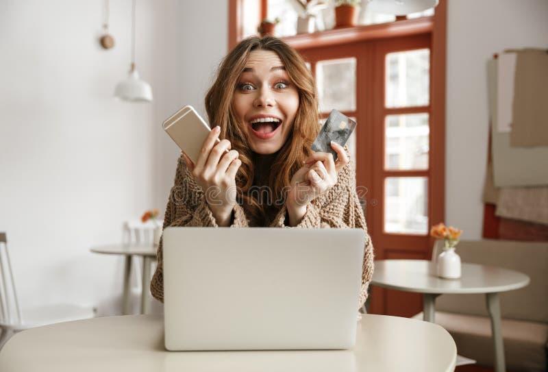 Excited молодая женщина 20s держа кредитную карточку и smartphone, whil стоковые изображения