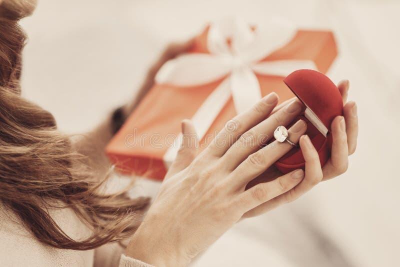 Excited молодая невеста пробуя роскошное кольцо с бриллиантом на ее безымянном пальце стоковые изображения rf