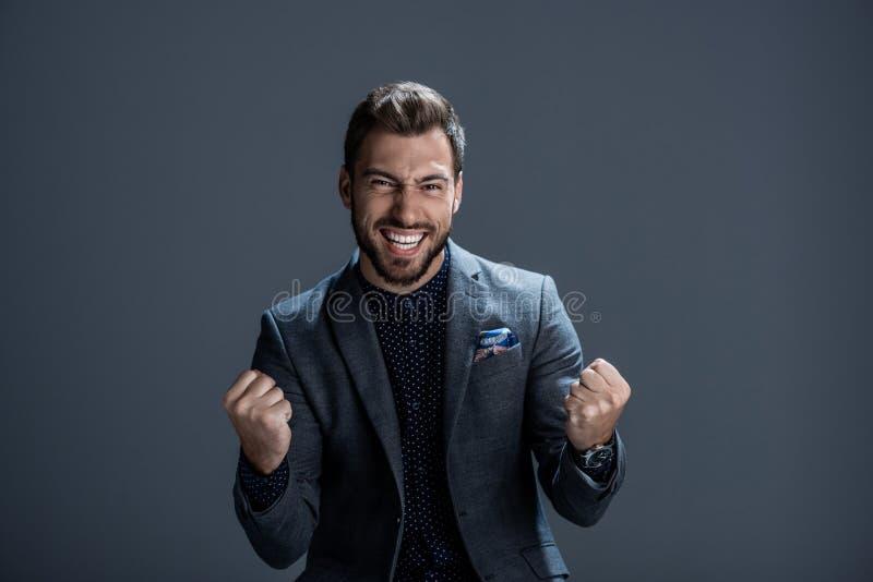 Excited молодой человек в официально костюме обхватывая его кулаки стоковое изображение