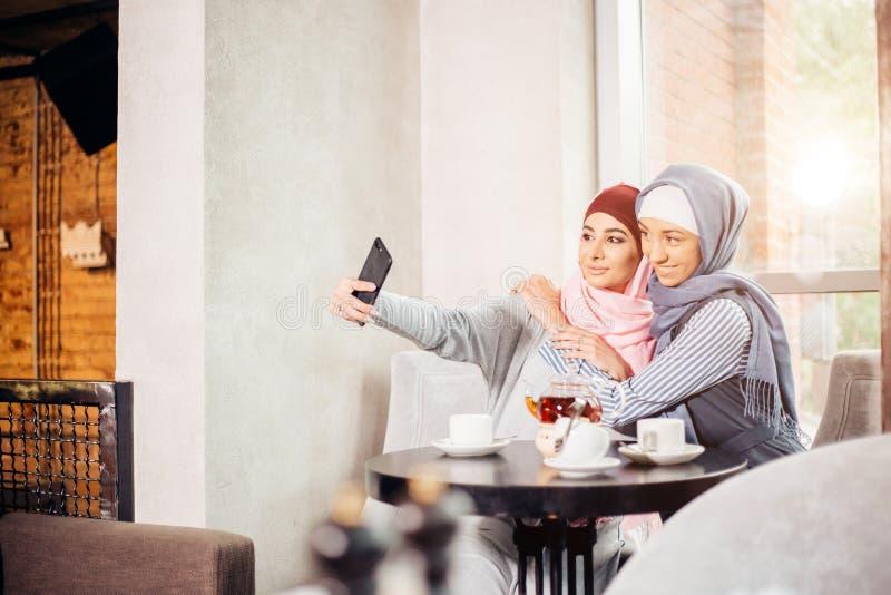 Excited молодые мусульманские подруги принимая selfie совместно стоковые фотографии rf